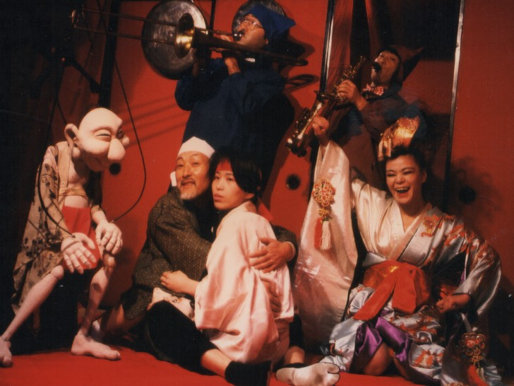 a group of people in traditional Japanese garb with two horn players and a marionettealr