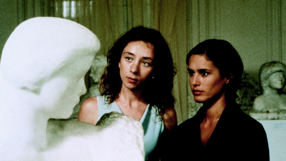 two women looking at a sculpture of a womanalr
