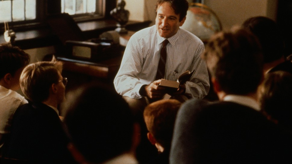 Robin Williams as John Keating sitting on a desk talking to his studentsalr