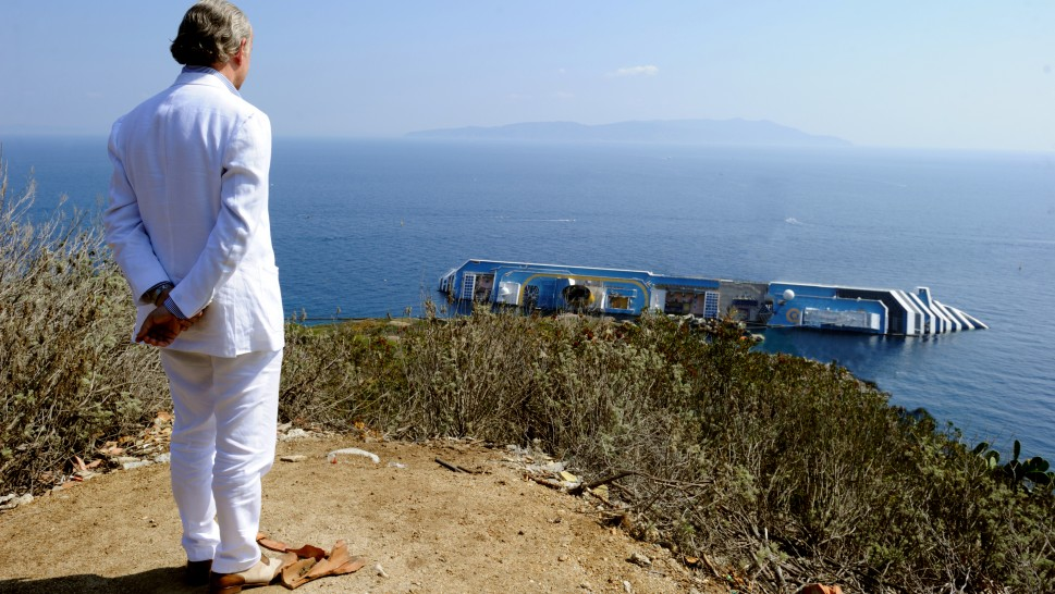 man in a white suit looking out at a sinking yachtalr