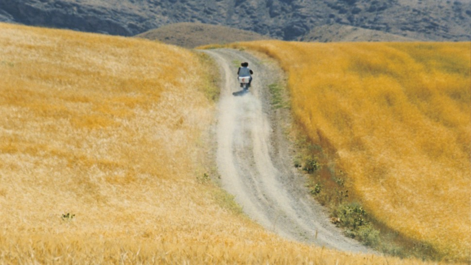 wide shot of a motorcycle on a winding road in the Iranian mountainsidealr