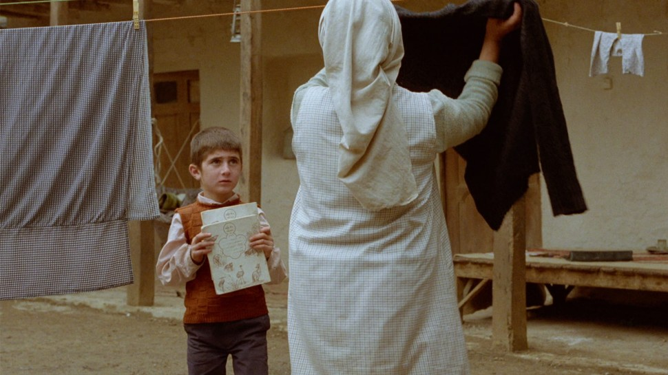 young boy talking to a woman hanging laundry