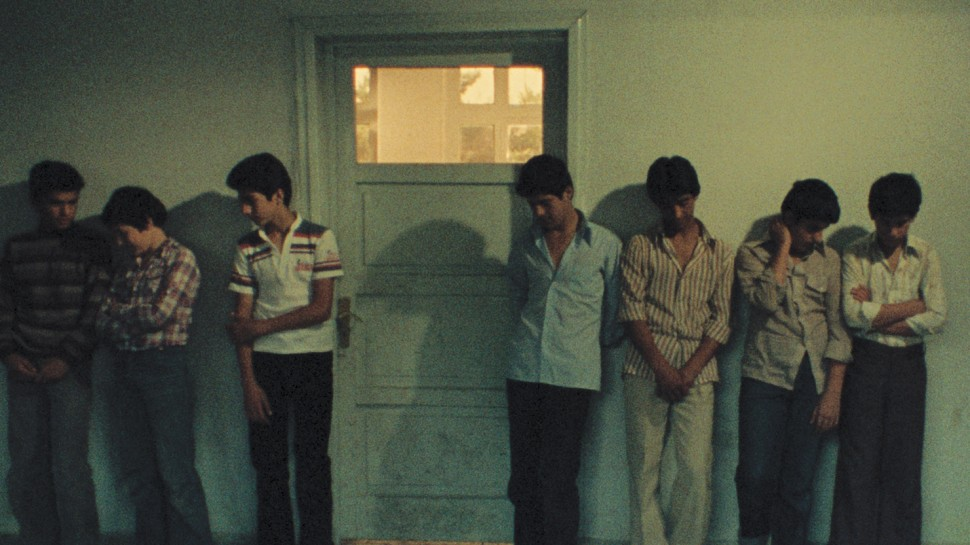 a line of young men standing against a wall, waitingalr