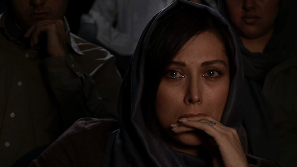 close-up of woman in movie theater watching film with tears in her eyesalr