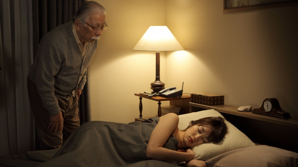 older man looking at a young woman asleep in a bed at nightalr