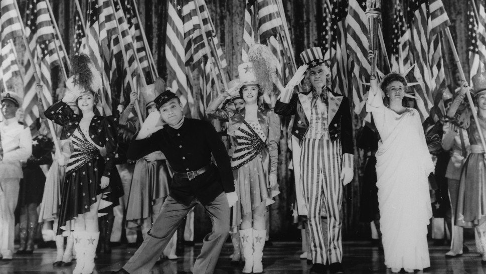 James Cagney and others on stage in a patriotic dance numberalr