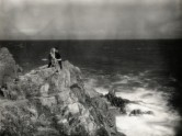 b/w photo of a woman and man on cliff by the ocean