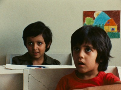 two young boys, one in front of the other, sitting at desks in a classroom