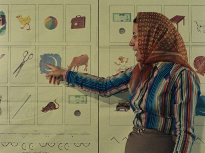 female teacher with headscarf pointing to a board with pictures and words