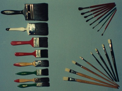 an array of paint brushes, large and small, lined up