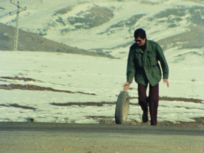 man rolling a tire along the road with a snowy mountain landscape behind him