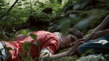 woman lying in forest at base of tree