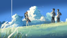 Two boys and one girl with backpacks on a grassy plateau against a blue sky with clouds