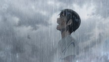 boy looking up and smiling in a rainstorm
