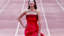 woman in red formal dress laughing on a running track