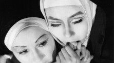 a close-up of two nuns, one holding the other's hands up to her mouth
