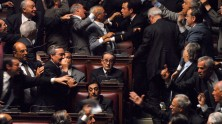Toni Servillo as Giulio Andreotti sitting still in the midst of a chaotic government chamber