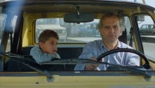 young boy in the passenger seat next to older man driving a car
