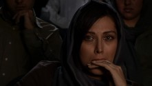 close-up of woman in movie theater watching film with tears in her eyes