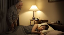 older man looking at a young woman asleep in a bed at night