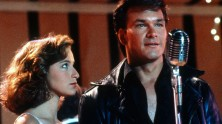 Jennifer Grey and Patrick Swayze on stage in front of a microphone